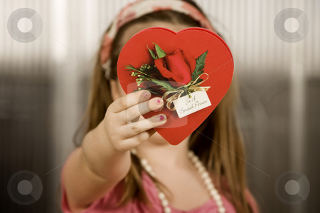 Young girl with Valentine stock photo, Cute little girl with a Valentine in front of her face by Scott Griessel