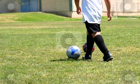 Soccer stock photo, Kid playing on a green field with soccer ball. by Henrik Lehnerer