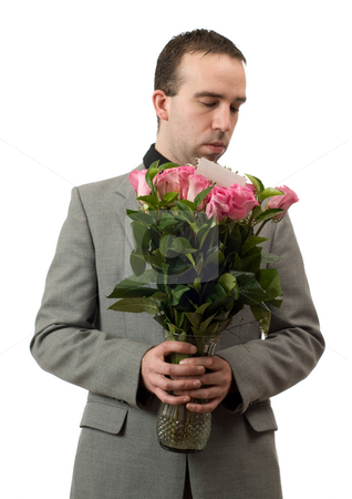 Man Smelling Roses stock photo, A young man wearing a formal suit is smelling some roses in a vase, isolated against a white background by Richard Nelson