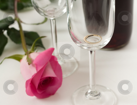 Ring In Wine Glass stock photo, A soft focus view of a ring in a wine glass, with a pink rose by Richard Nelson