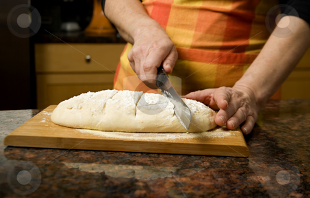 Adding cut to unbaked bread dough stock photo, Adding cut to unbaked bread dough with serrated knife by Scott Griessel