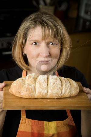 Woman in Kitchen with Bread stock photo, Woman in a residential kitchen with bread by Scott Griessel