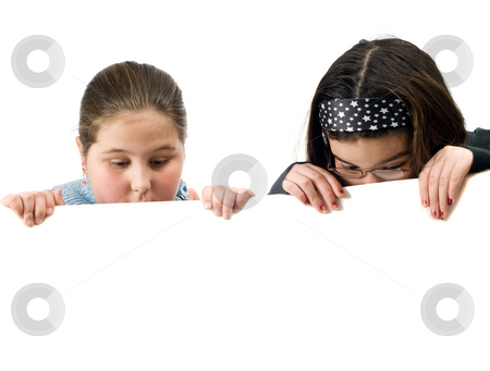 Two Kids Spying stock photo, Two young girls looking over a white wall at something by Richard Nelson