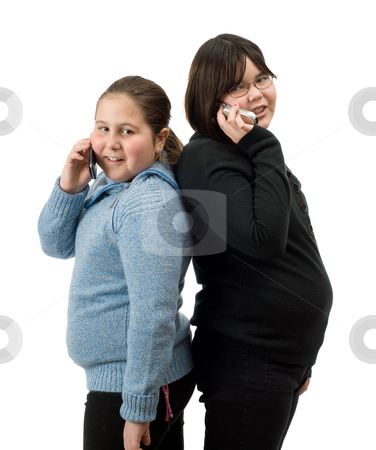 Two Girl On Their Cell Phones stock photo, Two young girls standing back to back, talking on their cell phones, isolated against a white background by Richard Nelson
