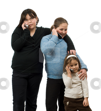 Three Girls Talking On Cell Phones stock photo, Three young girls of different ages, talking on their cell phones, isolated against a white background by Richard Nelson