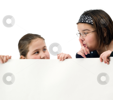 Be Quiet stock photo, Two young girl trying to spy over a white wall, isolated against a white background by Richard Nelson