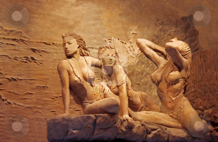 Stone Statue stock photo, A stone statue of three women on a rock by Kevin Tietz