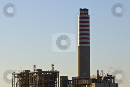 Power plant stock photo, View of a power plant with an high chimney at sunrise by Massimiliano Leban