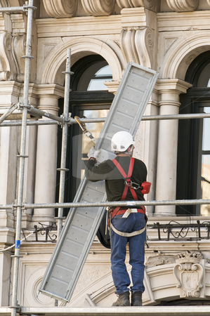 Worker stock photo, Workman putting up scaffolding by Massimiliano Leban