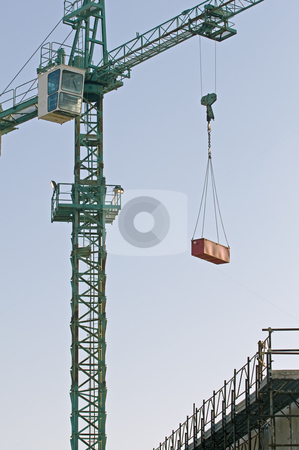 Crane stock photo, Crane lifting meterial in a construction site by Massimiliano Leban