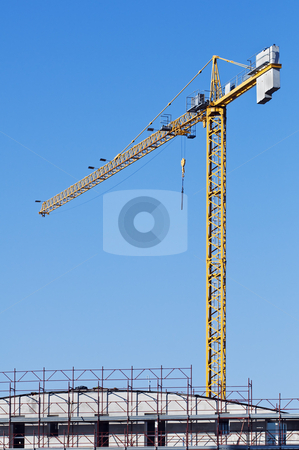Crane stock photo, Yellow crane in a contruction site abd a building with scaffolding by Massimiliano Leban