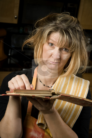 Harried woman with recipe book stock photo, Harried woman in residential kitchen with recipe book by Scott Griessel