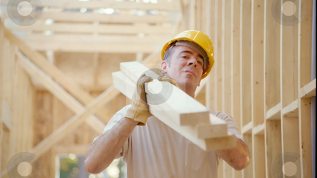 Construction Worker stock photo, A worker carries wood to the job site. by Jordan Edgcomb