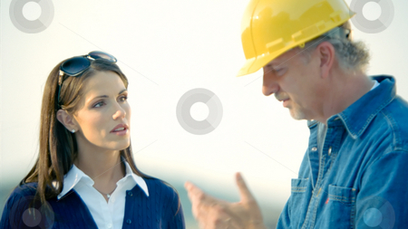 Construction 01 stock photo, Construction workers look at and discuss plans. by Jordan Edgcomb