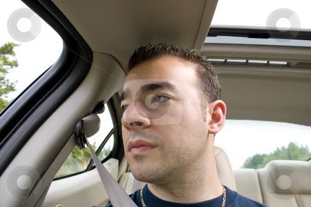 Bored Car Passenger stock photo, A young man is bored and stares out the window while riding as a passenger on a long road trip by Todd Arena