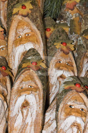 Wooden gnomes stock photo, Lot of gnomes faces painted on wood by Massimiliano Leban