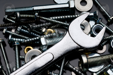 A close-up of various nuts, blots and screws and an open ended w stock photo, A close-up of various nuts, blots and screws and an open ended wrench on a black reflective surface by Vince Clements