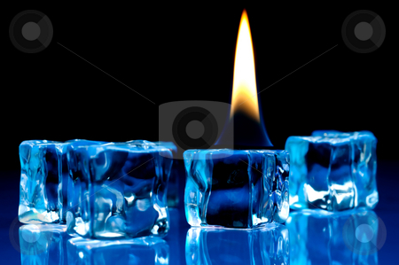 Flame burning on blue ice cubes stock photo, Hot flame burning on cold blue ice cubes on a reflective surface by Vince Clements