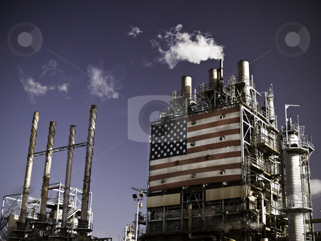 Refinery Complex stock photo, Part of an oil refinery complex with a big American flag at the front. Fumes coming out of the chimney (low angle view). by Dmytro Bershadskyy