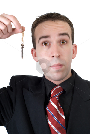 Businessman Holding Key stock photo, A young businessman wearing a suit, holding an old key, isolated against a white background by Richard Nelson