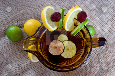 Summer punch drink stock photo, A jug containing punch and surrounded with fruit on a hessian background by Paul Phillips