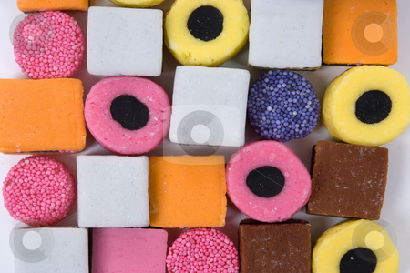 Licorice sweets round and square arranged as a background stock photo,  by Paul Phillips