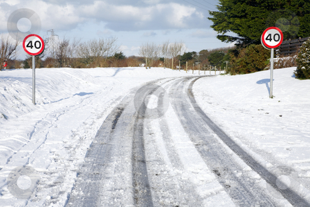 Snow tracks on a country road and 40 mph signs. stock photo, Snow tracks on a country road and 40 mph signs. by Stephen Rees