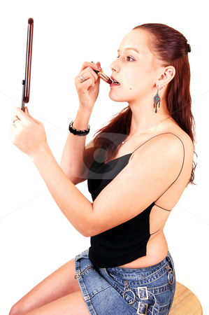 A pretty woman fixing her lips. stock photo, A beautiful young woman touching up her make-up and holding up an hand held mirror. by Horst Petzold