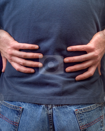 Back Pain stock photo, Closeup view of a man holding his back in pain by Richard Nelson