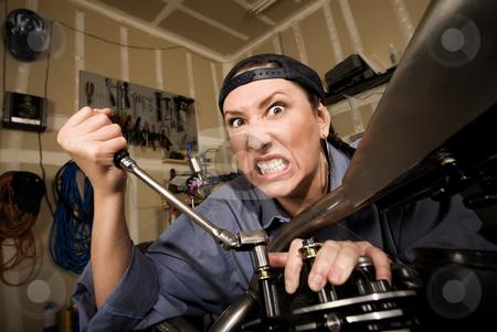 Funny Female Hispanic Mechanic stock photo, Funny female Hispanic mechanic  working on a chopper style motorcycle by Scott Griessel