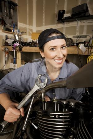 Female Hispanic Mechanic stock photo, Female Hispanic mechanic working on a chopper style motorcycle by Scott Griessel