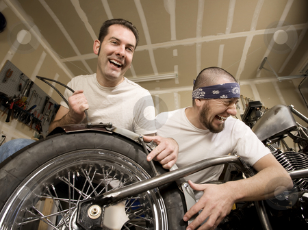Laughing Motorcycle Mechanics stock photo, Two laughing men working on a chopper-style motorcycle by Scott Griessel