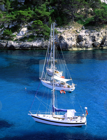 Three in a row stock photo, Three sailboats just of the cost of Minorca, Spain by Paul Phillips