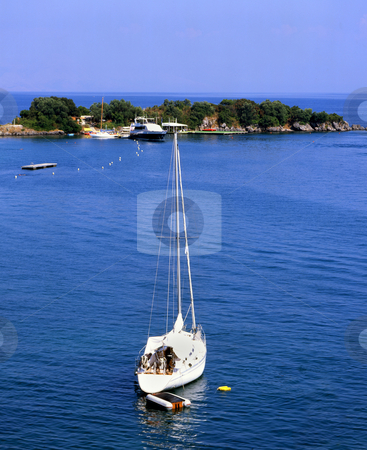 Off the island stock photo, Small white sailboat just off the coast of a small island, near Corfu, Greece by Paul Phillips