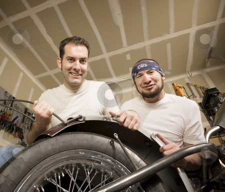 Two Motorcycle Mechanics Placing a Fender stock photo, Two men working on a chopper-style motorcycle by Scott Griessel