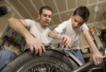 Father and son in garage stock photo, Father and son working on motorcycle in garage by Scott Griessel