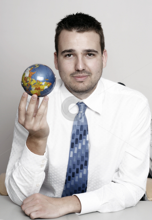 Businessman holding globe stock photo, Businessman holding and examing globe, conceptual usage by Christopher Meder