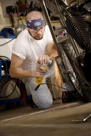 Hispanic man using grinder on motorcycle stock photo, Hispanic man using grinder tool on the front fork of motorcycle by Scott Griessel