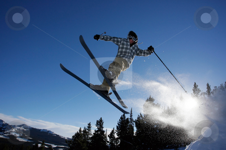 Ski Jump stock photo, A young man flies through the air after hitting a ski jump in the back country. by Jordan Edgcomb