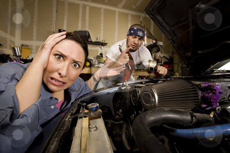 Frustrated woman with incompetent mechanic in background stock photo, Frustrated woman leaning on car with incompetent male mechanic in background by Scott Griessel