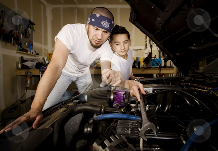 Hispanic father and son in garage stock photo, Hispanic father and son working on car engine in garage by Scott Griessel