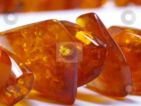 Amber bead stock photo, Detail amber bead on off- white background close up by Torsten Lorenz