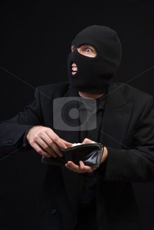 Thief stock photo, A thief wearing a balaclava snooping through a wallet, shot against a dark background by Richard Nelson