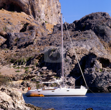 Rocky Harbor stock photo, A sailboat moored by a small cove just outside of Lindos on the Greek island of Rhodes by Paul Phillips