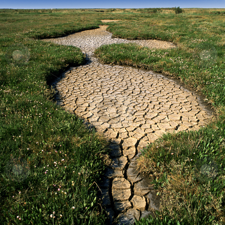 Drought hits stock photo, Cracked and dry earth. Formed after a period of drought in an open field. by Paul Phillips
