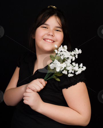 Childhood Portrait stock photo, A young girl holding some silk flowers, shot against a black background by Richard Nelson