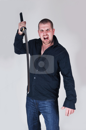 Dangerous young man. stock photo, An very angry and dangerous young man wit a long sword screaming at the photographer, with light gray background. by Horst Petzold