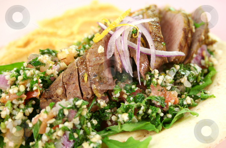 Middle Eastern Lamb Pita Bread  stock photo, Sliced Middle Eastern lamb fillet with hummus and tabouleh. by Brett Mulcahy