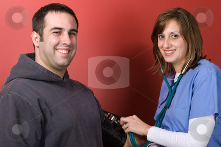 Checking Blood Pressure stock photo, A young nurse checks the blood pressure of her patient. by Todd Arena