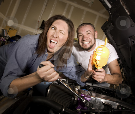 Hapless mechanics stock photo, Hapless mechanics working on car engine getting in each others way by Scott Griessel